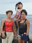 THREE GENERATIONS POSE FOR A PHOTO ON HAVANA SEA WALL WALK.