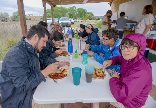 A morning monsoon drizzle dampens breakfast as students prepare for a wet day in the field.