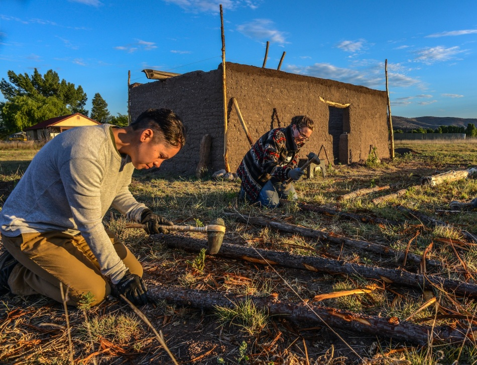 DIANAN TREVIZO (Clovis, NM) and ALEXANDRA NORWOOD (Pasadena CA) work with three quarter groove axes to remove the back from these ridge poles for the Pueblo's roof.