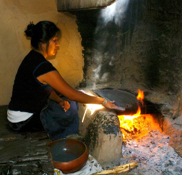"Annetta Koruh ""Nita"" bakes Piki Bread for her godson's Naming ceremony and to feed the Kachinas that come to dance at 3rd Mesa.    The baker dips their hand in a mixture of cornmeal, crisco, and sheep brains plies the mixture thinly upon a flagstone rock which bakes the bread."